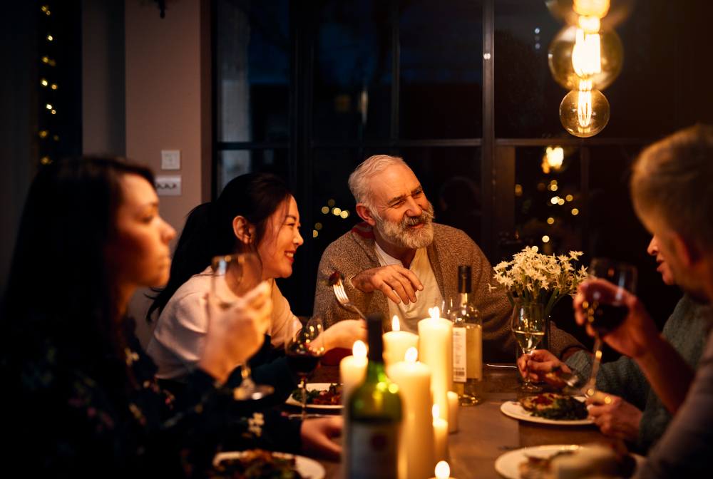 Cheerful Guests At Dinner Table Listening To Friend And Drinking Wine