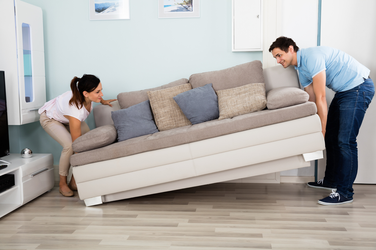 Couple Placing Sofa In Living Room